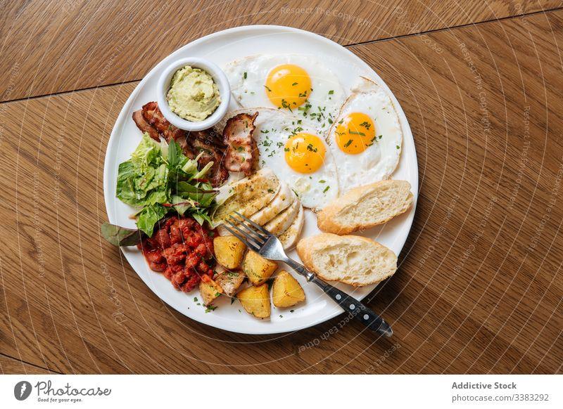 Leckere Frühstücksmahlzeit mit Spiegeleiern und Gemüse Englisch Ei gebraten Zuprosten Speck Bohne Kartoffel Salatbeilage Küche Speise Teller Tisch Kalorie