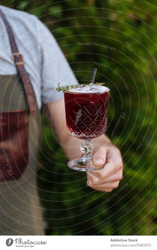 Anonyme Kellnerin hält rotes appetitanregendes Getränk im Glas trinken frisch Cocktail lecker geschmackvoll Beeren organisch festlich Alkohol Frucht Saft
