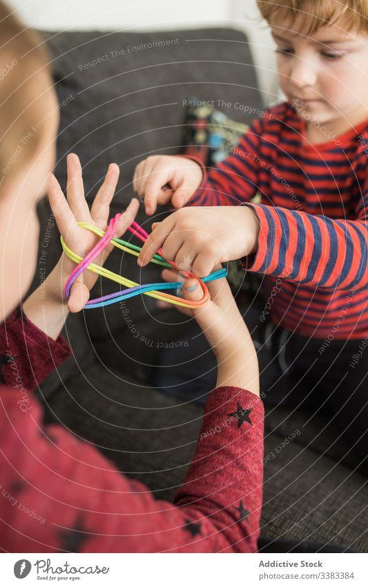 Kluge Kinder benutzen Gummibänder beim Spiel Band kreativ farbenfroh lernen Erziehung spielen elastisch Zusammensein wenig Handfläche verdrehen lässig heimwärts