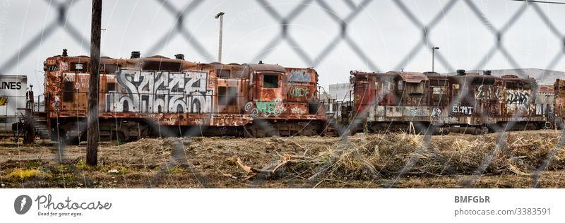 besprayte Zugwagen hinter einer Absperrung Zugabteil Sprayerei gitterzaun transportmittel Eisenbahn Bahnfahren Menschenleer Tag Schienenverkehr Verkehr