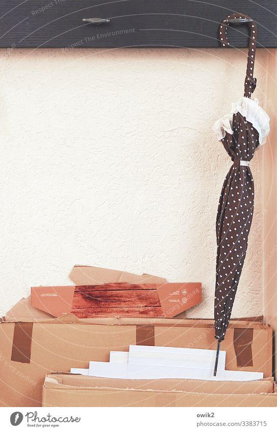 Schirm, der am Haken hängt Café Garderobe hängen Wand Innenaufnahme Menschenleer Tag aufhängen weiß Karton Verpackungsmaterial Pappe Ordnung ästhetisch