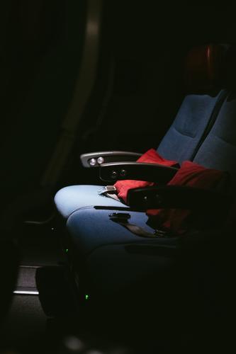 Eine Reihe Sitze im Flugzeug mit roten Kissen und Anschnallgurten im dunklen Flugzeugsitz fliegen Reisen tourismus Nacht dunkel düster leer Sitzplatz