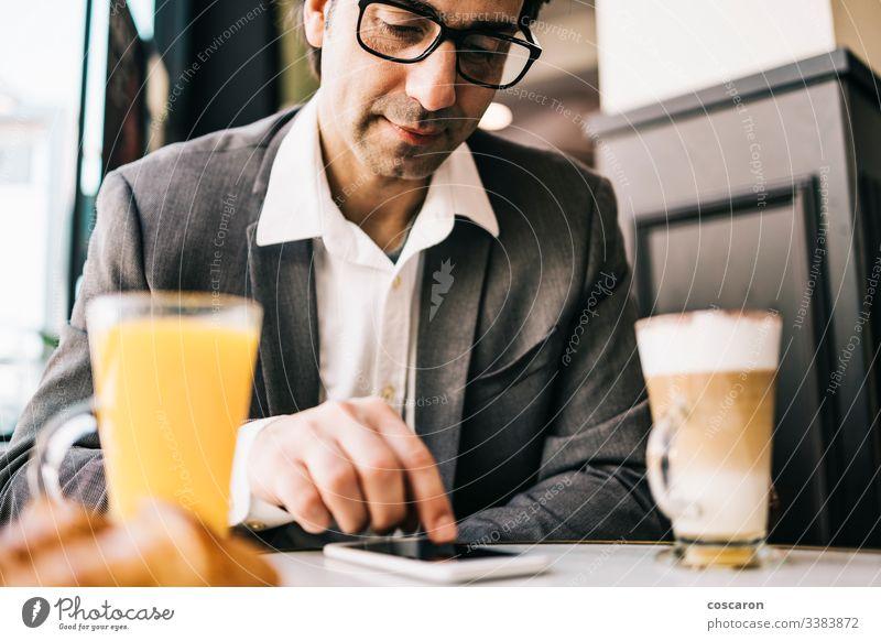 Geschäftsmann an der Bar bei einer Tasse Kaffee und Orangensaft Erwachsener Anwendung Frühstück Business Café heiter Mitteilung trinken Exekutive Ausdrücken