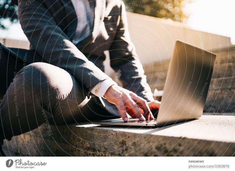 Lächelnder junger Geschäftsmann sitzt auf der Treppe mit Laptop und Kaffee. Erwachsener Vollbart bärtig Business Kaukasier Großstadt Computer Konzept Anschluss
