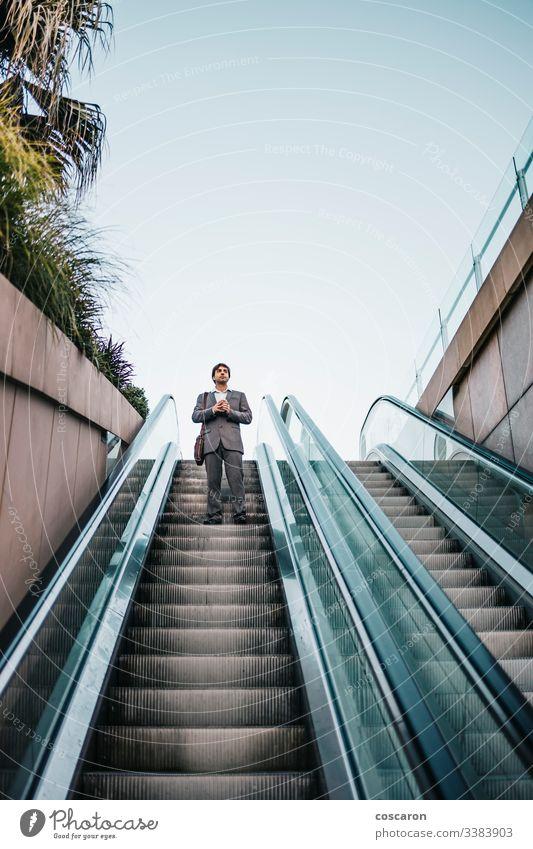 Geschäftsmann im Anzug, der einen Kaffee trinkt und eine Rolltreppe hinauffährt Erwachsener Flughafen attraktiv Chef Business Geschäftsleute Geschäftskleidung