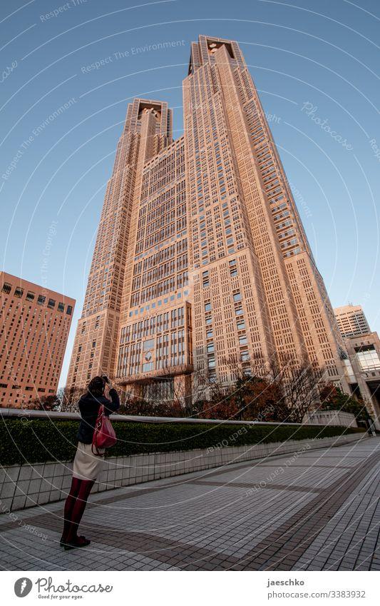 Junge Frau fotografiert Hochhaus in Japan Architektur Tokio Tokyo Rathaus Wolkenkratzer Tourismus Stadtrundgang hoch Haus futuristisch Stadtzentrum Bauwerk