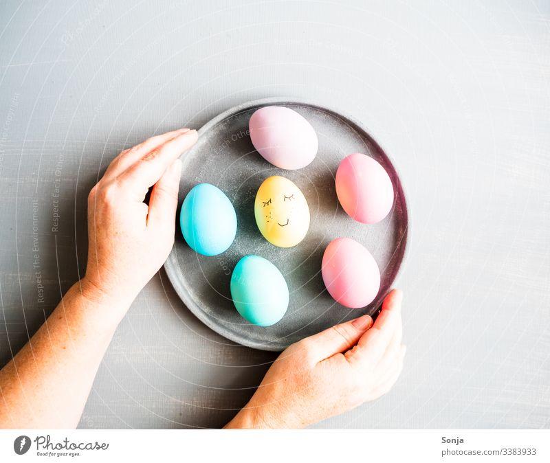 Hände halten einen Teller mit Ostereiern bemalt hand frau tisch grau draufsicht aufgemaltes gesicht humor lustig ostern teller Pastellfarben Foodfotografie