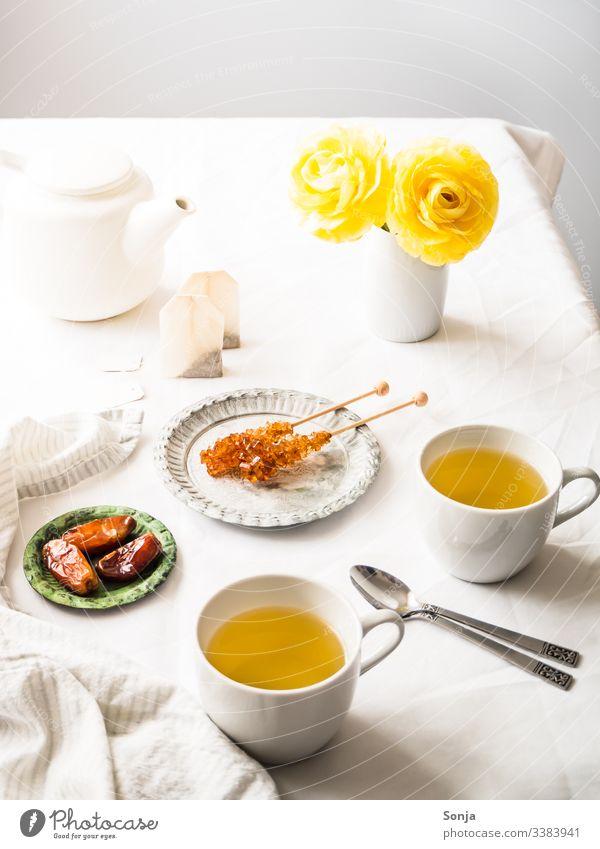 Kräutertee mit gelben Blumen auf einem weißen Tischtuch kräutertee heiß teekanne teebeutel kandiszucker Teepause tischtuch weiss datteln getränk Frühstück