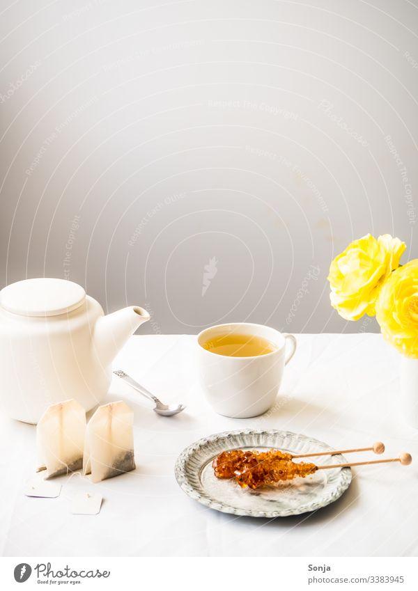 Teepause mit Kräutertee und Kandiszucker Fahne Frühling kräutertee kandiszucker teekanne Zauberstab weiss teebeutel löffel tasse heiß getränk süß tischtuch