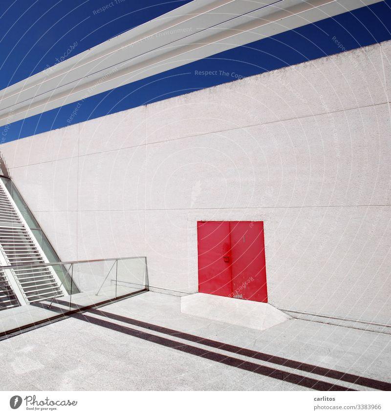 Rote Tür an weißer Wand mit blauer Linie unter blauem Himmel Fassade Tor rot Markierung Linien Fugen Schatten Geländer Glas Lamellen Sonnenschutz menschenleer
