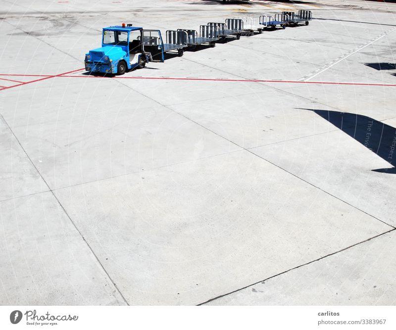 Gepäckwagen ohne Gepäck auf dem Flughafen an der Parkposition eines schattenwerfenden Flugzeuges Transport Zugmaschine Anhänger Markierungen Linien rot blau