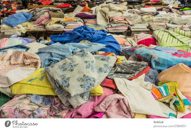 Wühltisch und gefaltete Textilien im Hintergrund second hand Stoff Bekleidung gebraucht Second hand Laden Durcheinander bunt Stapel preisgünstig Recycling