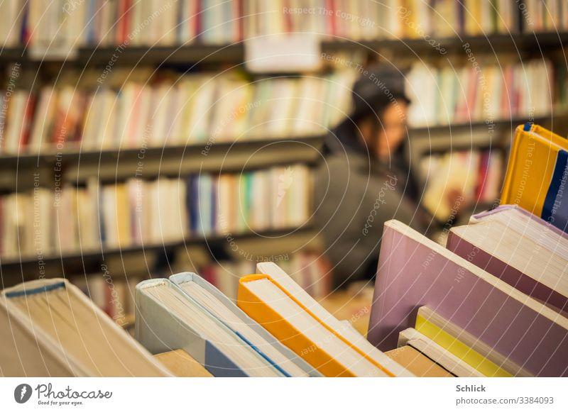 Nahaufnahme second hand Bücher im Buchladen mit Kundin im Unschärfebereich bücher Second-Hand Laden kundin Frau selektiver Focus Bokeh Bücherregal viele