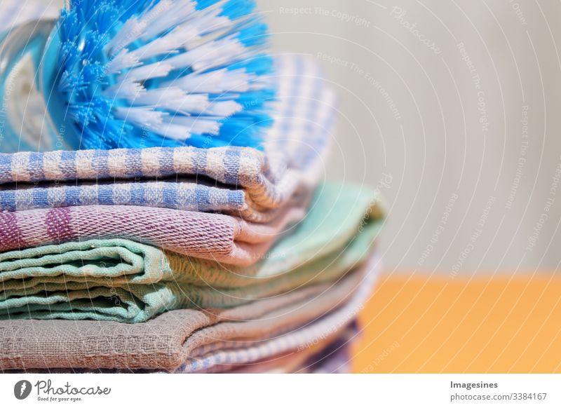 Geschirrhandtücher und Spülbürste auf gelbem Hintergrund, Leinen und Baumwolltücher. Stapel bunte Geschirrtücher Küche gelber Hintergrund Leinentuch Spülen