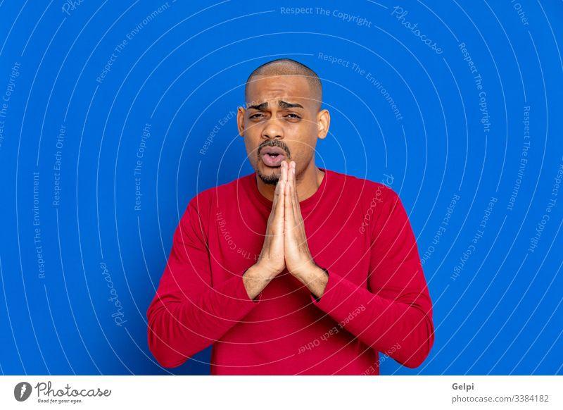 Afrikanischer Typ mit rotem Trikot schwarz blau Fragen beten Faust Glaube Gläubiger Meditation christian katholisch Erwachsener Menschen Person männlich