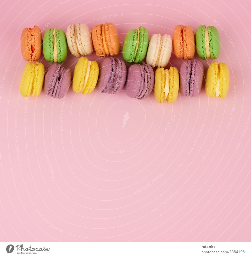 gelbe, violette runde gebackene Makkaronentorten auf rosa Hintergrund, Dessert liegt in einer Reihe Macaron Makrone Schaumgebäck niemand Gebäck Haufen purpur