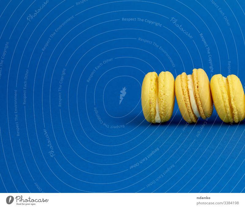 gelbe, zitronenfarbene, runde Makronenkuchen auf dunkelblauem Hintergrund Macaron Schaumgebäck niemand Ernährung Gebäck Haufen Reihe Belegtes Brot Kulisse Snack