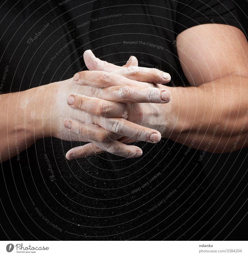 muskulöser Athlet in schwarzer Uniform reibt seine Hände mit weißer, trockener Sportmagnesia ein Pulver Kraft vorbereitend gestreut Sportler sportlich Stärke