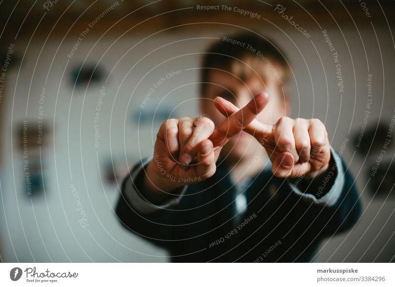Junge macht ein Kreuz mit den Fingern Kindheit Kinderspiel Hände Symbole & Metaphern symbolkraft symbolisch Symbolismus drehen gedreht Mittelfinger