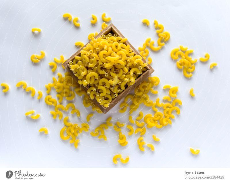 Ungekochte gelbe Nudeln auf dem weißen Grund. Spätzle Speisekarte Lebensmittel Küche Makkaroni Italienisch Essen roh Penne Gesundheit Textur vereinzelt