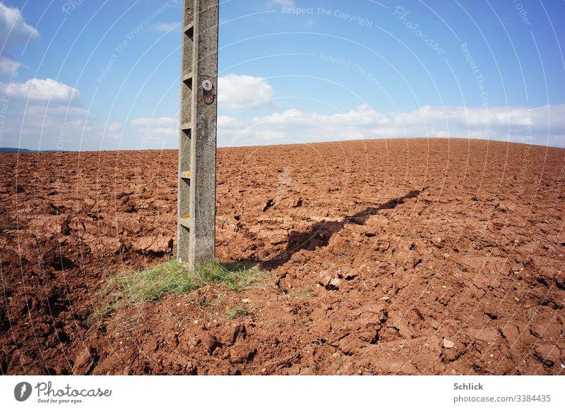 Acker mit nackter Erde und Strommast mit Schild Lebensgefahr unter blauem Himmel Monokultur Text Pestizide Gefahr Landwirtschaft Hinweis doppeldeutig braun weiß