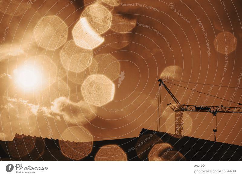 Hochbau im Regen Kran hoch Metall Baukran Baustelle Dächer Himmel Wolken Abendrot Sonne Sonnenlicht Gegenlicht Regentropfen Wassertropfen Fensterscheibe nass