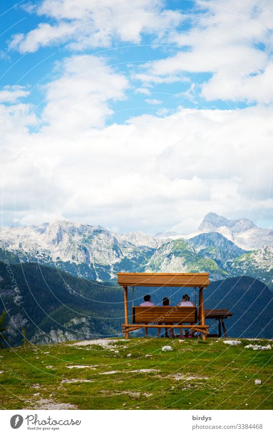 Touristen sitzen auf einer Bank oder Schaukelbank auf dem Gipfel des Berges Vogel in Slowenien und bestaunen das vor ihnen liegende Alpenpanorama . im Dreiländereck Slowenien - Österreich und Italien. Skigebiet Vogel, Slowenien