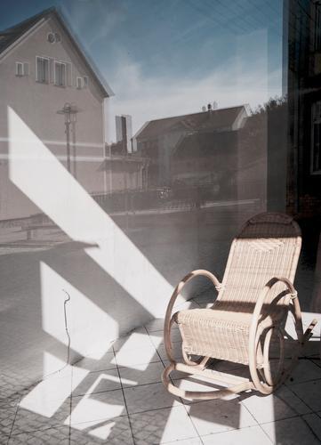 Feierabendheim Schaufenster Spiegelung Reflektion Sonnenlicht Schatten Kontast Häuser Himmel Fenster Dächer urban Schaukelstuhl Ruhe friedlich Stilleben