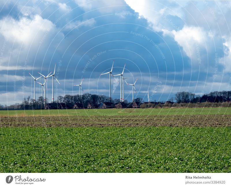 Windräder nahe Wohnhäusern und Feldern Windpark Repowering Farbfoto Landschaft Erneuerbare Energie Wetter Wolken Regenwolken Außenaufnahme Natur Umwelt