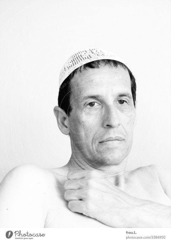 Die Faust auf der nackten Brust und über dem leeren Blick die weiße Häkelmütze auf dem schwarzen Haar ärgerte er sich über das schlechte Fernsehprogramm Mann