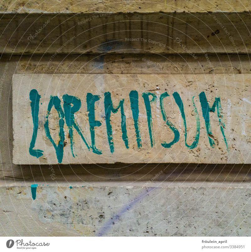 LOREMIPSUM - Typografie an Sandsteinwand Zeichen Farbfoto Schriftzeichen Außenaufnahme Schilder & Markierungen Tag Wand Haus Textfreiraum unten Fassade