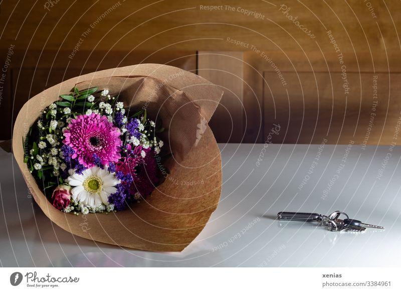 Blumenstrauß und Schlüssel auf hellem Tisch Dekoration & Verzierung Häusliches Leben Lifestyle Zuhause Wohnung Schlüsselbund Holzbank Esstisch nach hause kommen