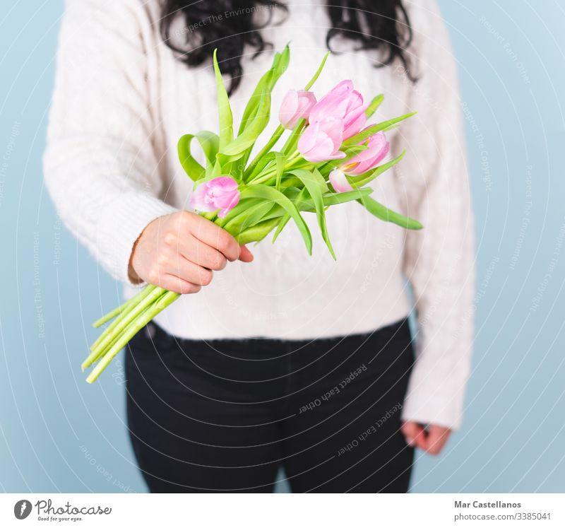 Frau in einem weißen Pullover mit einem Strauß rosa Tulpen. Frühjahrskonzept. Mutter Liebe romantisch Valentinsgruß Glamour Gruß präsentieren Hochzeit