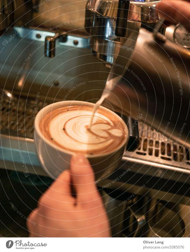 Milch, die Milchkaffee-Kunst in die Kaffeetasse gießt Latte Getränk heiß Café Latte Tasse auf Espresso-Basis Kaffeehaus doppelter Espresso Latte Art Heißgetränk