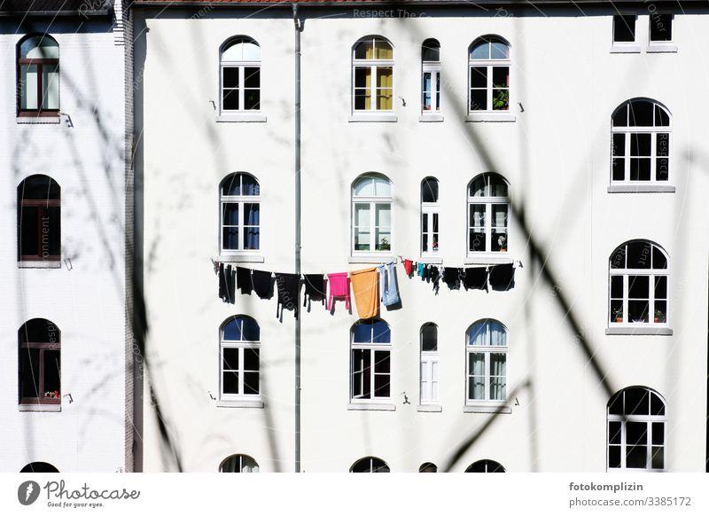 Wäscheleine an Hausfassade Wäsche waschen Altbau Mehrfamilienhaus Waschtag Bekleidung Haushalt trocknen aufhängen wäsche aufhängen Fenster Häusliches Leben Seil