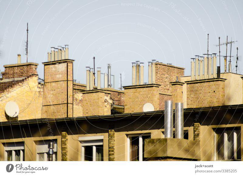 Sammlung von Schornsteinen und paar Antennen nebeneinander Dach Symmetrie Nostalgie Klima Wolkenloser Himmel Fenster oben Sonnenlicht Kontrast Tag