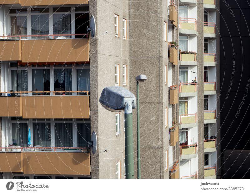 Schöneres Wohnen und die Straßenlaternen Zentralperspektive Starke Tiefenschärfe Sonnenlicht Tag Zeitgefühl Wohnhochhaus Umwelt trist modern authentisch Fassade