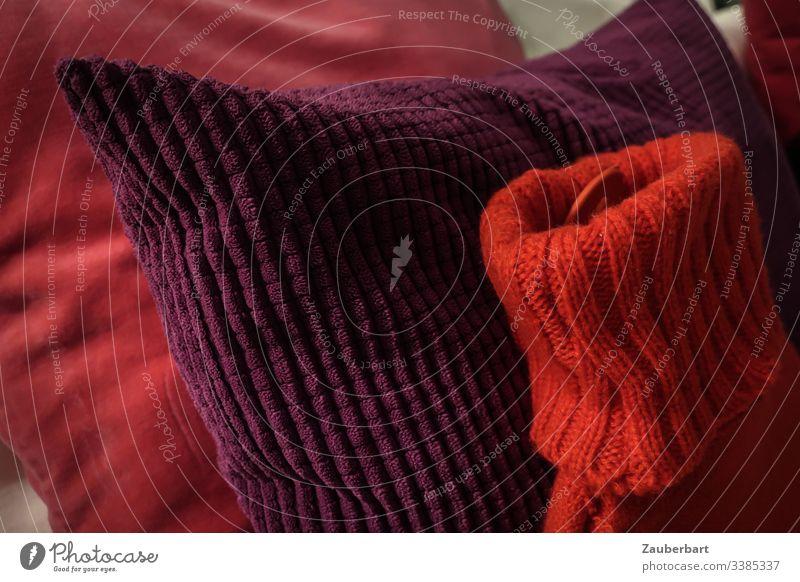 Wärmflasche im Pullover mit befreundeten Kissen in rot und lila Strickwaren gemütlich anlehnen Freundschaft Wärme Farbfoto Innenaufnahme Wolle gestrickt weich