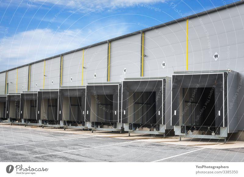 Verladerampen für Industrielager. Lagertüren. Offene Tore Zugangstüren Blauer Himmel Gebäude Business Frachtlager Versand Verteilung Docks Türen leer Eingang