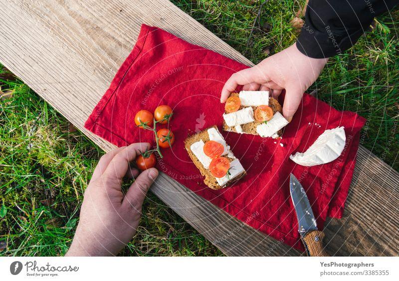 Essen im Freien auf Gras servieren. Picknick im Sonnenlicht auf einem Holzbrett obere Ansicht Brot Pause Camping Käse Garten Feinschmecker packend grünes Gras