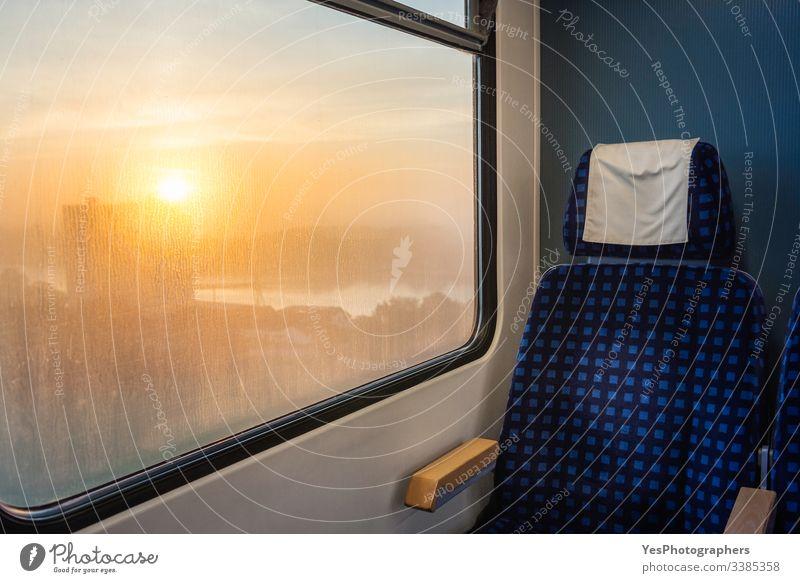 Zuginnenraum mit Stuhl und Sonnenaufgangsansicht am Fenster. Zugfahren Deutscher Zug Deutschland blauer Stuhl Wagen bequem Arbeitsweg umweltfreundlich