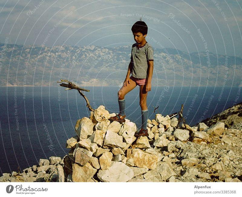Junges attraktives Kind besteigt einen Berg mit einem Stock in Unterhose Berge u. Gebirge Bergkette Bergkamm blau wandern Bergsteigen Natur Landschaft Abenteuer