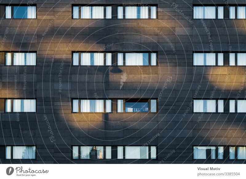 Nachmittagslicht über der schwarzen Fassade eines städtischen Gebäudes Fenster Reihen Struktur Architektur abstrakt Gebäudefassade urban Stadtfassade Farbe