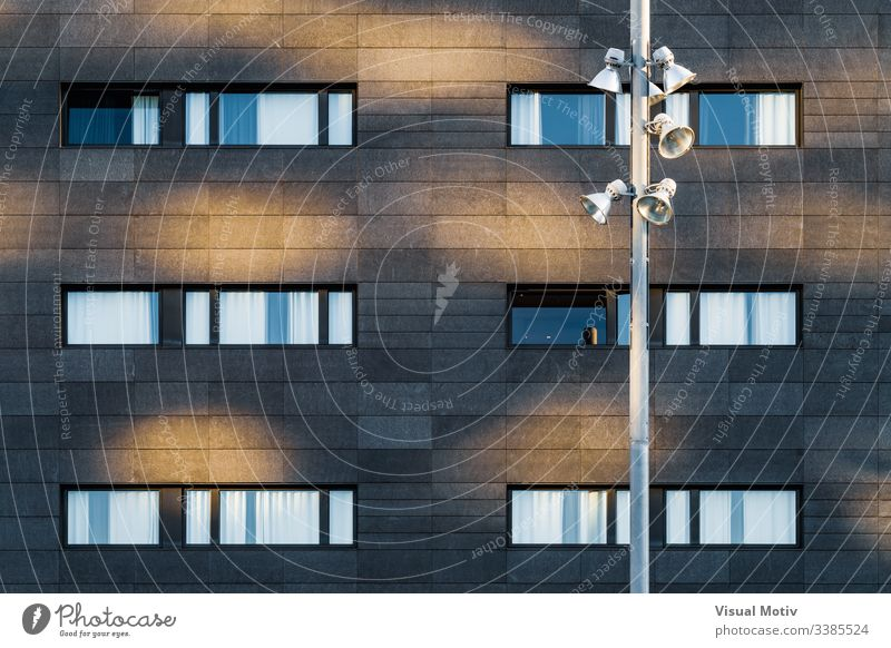 Straßenlampe und schwarze Fassade eines städtischen Gebäudes Fenster Reihen Struktur Architektur abstrakt Gebäudefassade urban Stadtfassade Farbe Außenseite