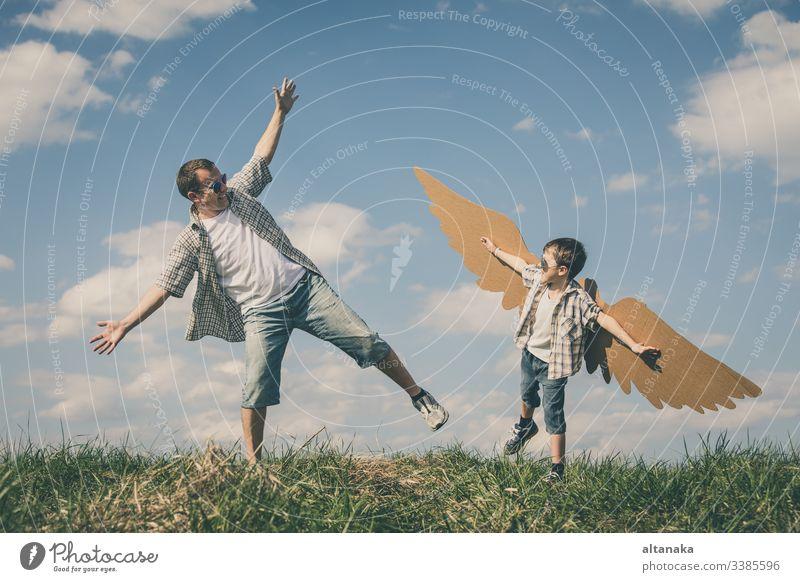 Vater und Sohn spielen mit Spielzeugflügeln aus Pappe Kind im Freien Familie Menschen Eltern Lifestyle Zusammensein Spaß Tag Junge Sommer Fröhlichkeit Papa Mann