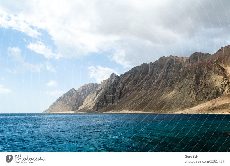 blaues Meer und hohe felsige Berge gegen den Himmel und Wolken in Ägypten Dahab Südsinai Naher Osten Rotes Meer Süd-Sinai Hintergrund Blaues Meer Tag hoch