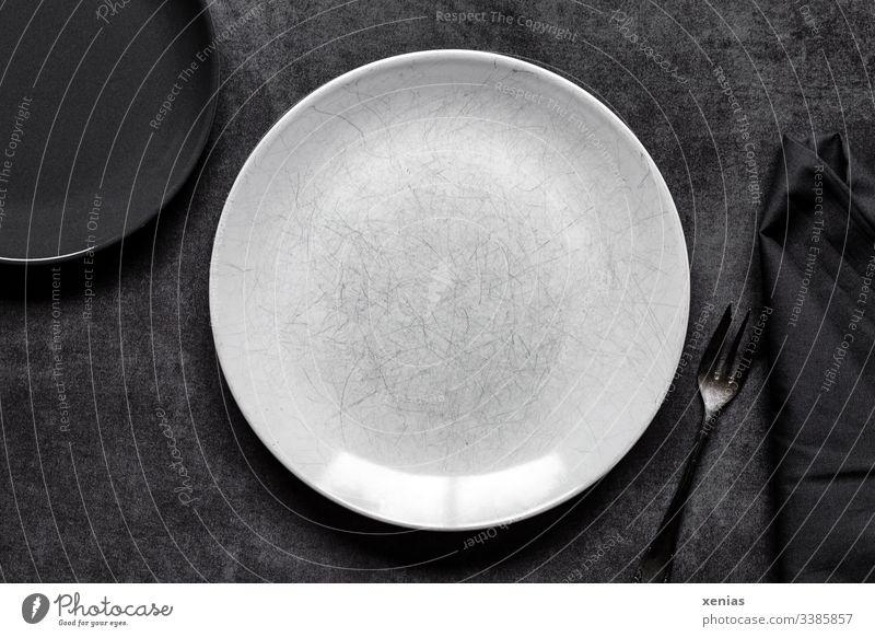 Heller und dunkler runder Teller mit Gabel auf grauem Untergrund leer Foodfotografie weiß Innenaufnahme Ernährung Serviette Tisch schwarz zerkratzt Essen dunkel