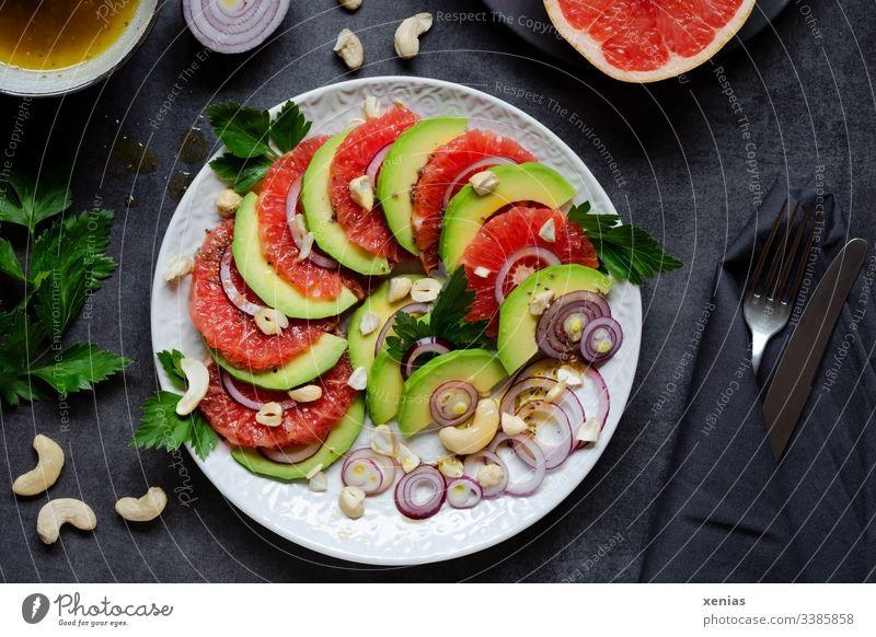 Salat mit Avocado, Grapefruit, Zwiebeln, Cashewnüsse und Petersilie auf weißem Teller angerichtet mit Messer und Gabel in schwarzer Serviette auf dunkler Tischplatte