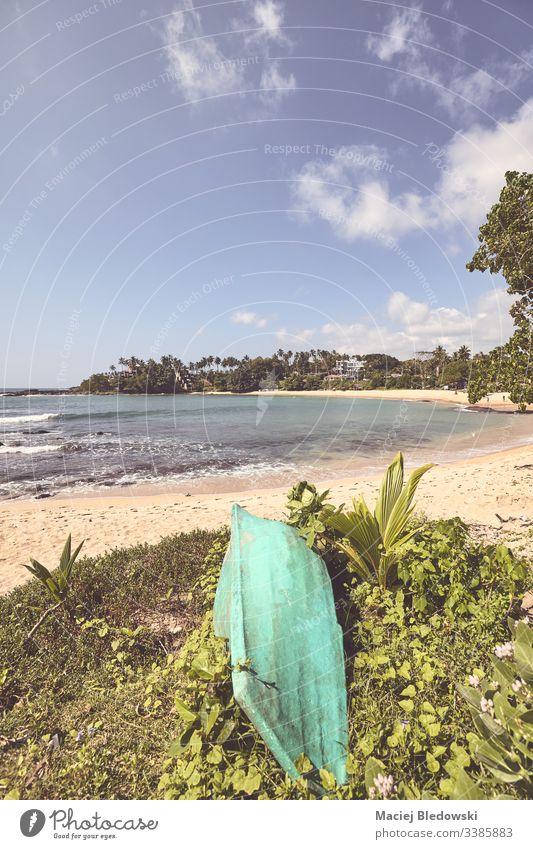 Retrofarbenes, stilisiertes Bild eines tropischen Strandes mit einem kleinen Boot. Sommer retro Instagrammeffekt gefiltert Sonne MEER Meer Urlaub Feiertag