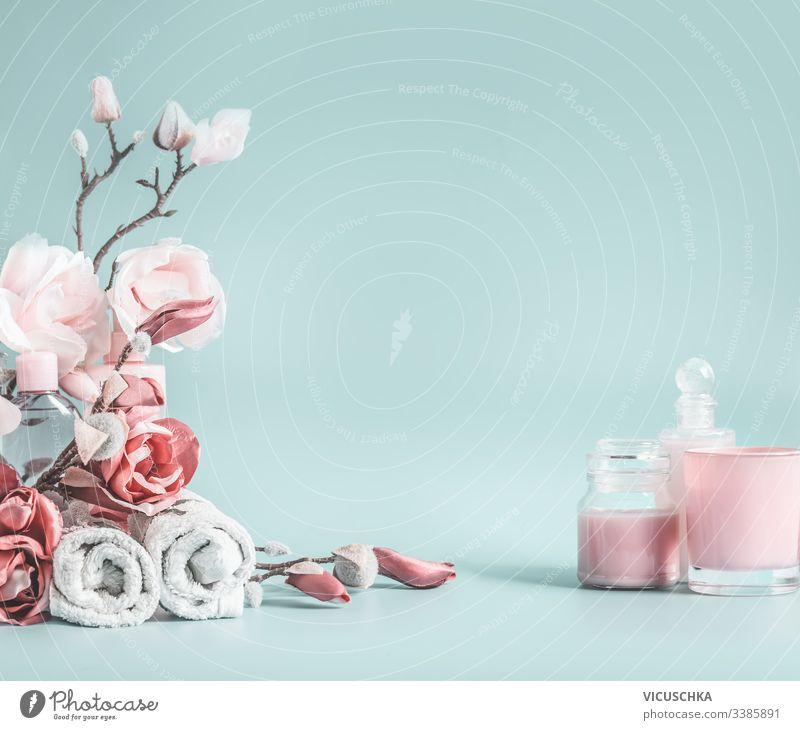 Schöner Hintergrund mit pastellrosa Blumen und Kosmetik auf pastellblauem Hintergrund Schönheitshintergrund Pastell Gesundheitswesen Schreibtisch modern blanko